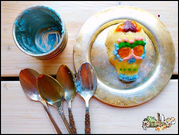 decorated sugar skull on plate with icing and spoons around
